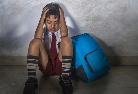 lifestyle dramatic bullying victim portrait of young sad scared hispanic kid 8 years old in school uniform and backpack sitting alone crying depressed and frightened suffering abuse being bullied