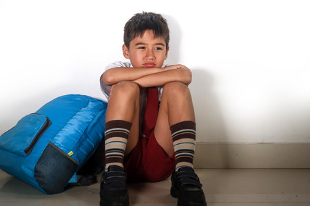 lifestyle dramatic bullying victim portrait of young sad scared kid 8 years old in school uniform and backpack sitting alone crying depressed and frightened suffering abuse problem being bullied Standard-Bild