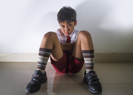 lifestyle dramatic bullying victim portrait of young sad and scared hispanic kid 7 - 10 years old in school uniform sitting alone crying depressed and frightened suffering abuse problem being bullied