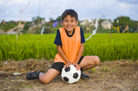 lifestyle portrait of handsome and happy young boy holding soccer ball playing football outdoors at green grass field smiling cheerful wearing training vest in kid education sport concept Stock Photo