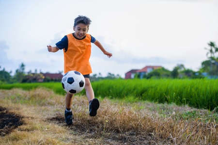 8 or 9 years old happy and excited kid playing football outdoors in garden wearing training vest running and kicking soccer ball , the kid having fun practicing sport Foto de archivo