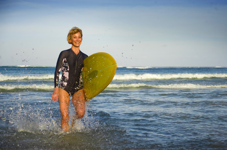 young attractive and happy blonde surfer girl in beautiful beach carrying yellow surf board walking out of the sea enjoying summer holidays at tropical island in in woman surfing lifestyle concept
