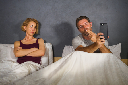 husband or boyfriend using mobile phone in bed and suspicious frustrated wife or girlfriend feeling upset suspecting betrayal and cheating in man woman couple relationship problem concept Stock Photo