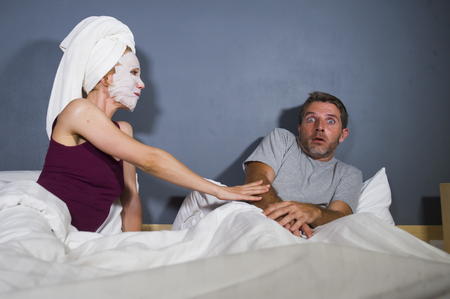funny lifestyle portrait of man and woman featuring weird married couple with wife in head towel and makeup face mask demanding sex to scared and reluctant husband rejecting her