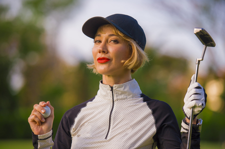 lifestyle outdoors portrait of young beautiful and happy woman at playing golf holding ball and putter club smiling cheerful in stylish golfing clothes isolated on green put background Archivio Fotografico