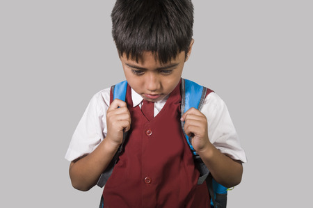 young kid 7 or 8 years old in school uniform and schoolbag feeling sad and depressed looking down scared and embarrassed victim of bullying and abuse in education social problem concept