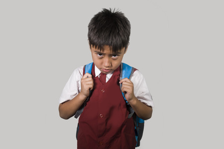 young child 7 or 8 years old in school uniform and schoolbag feeling sad and depressed looking down scared and embarrassed victim of bullying and abuse in education social problem concept