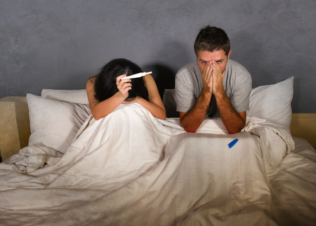 young couple in bed scared and stressed after positive result on pregnancy test with pregnant woman expecting unwanted baby and man feeling overwhelmed worried and disappointed Stock Photo