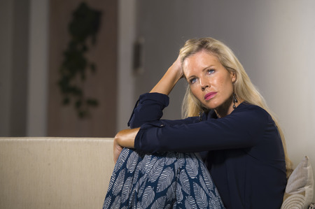 40s depressed and anxious beautiful blonde woman suffering depression feeling frustrated and lonely sitting at home sofa couch thoughtful and pensive in middle age crisis and life problem