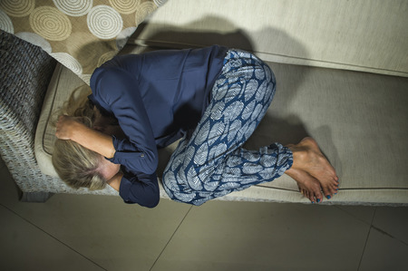 40s depressed and anxious beautiful blonde woman suffering depression and headache feeling frustrated crying sad at home in fetal position sofa couch desperate in pain and life problem Stock Photo