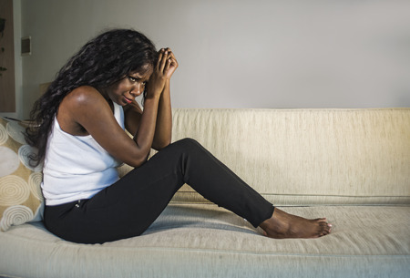 young attractive and sad black African American woman sitting depressed at home sofa couch feeling anxious and frustrated suffering depression problem and anxiety crisis crying desperate