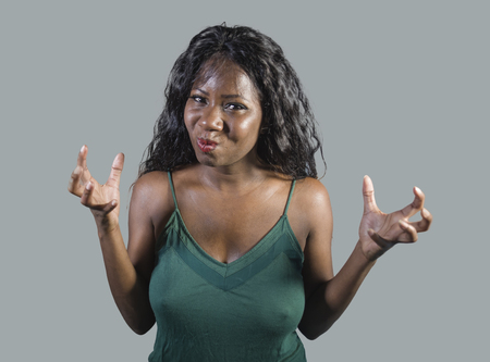 young beautiful and stressed black African American woman feeling upset and angry gesturing agitated and pissed looking crazy and furious arguing or having dispute isolated on studio background Stock Photo - 109057599