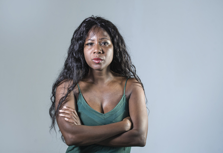 young beautiful and stressed black African American woman feeling upset and angry looking serious and pissed posing with folded arms on isolated studio background in moody face expression Stock Photo