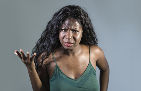 young beautiful and stressed black African American woman feeling upset and angry gesturing agitated and pissed looking crazy and furious arguing or having dispute isolated on studio background Stock Photo