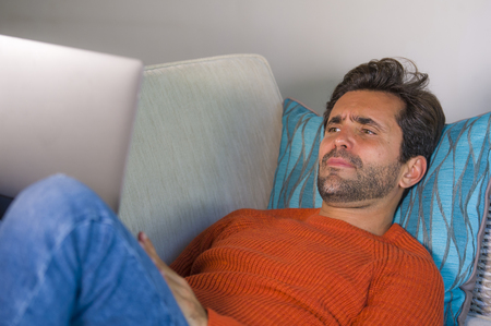 young happy and attractive man working relaxed with laptop computer at modern apartment living room lying at sofa couch typing and networking in entrepreneur success and lifestyle concept