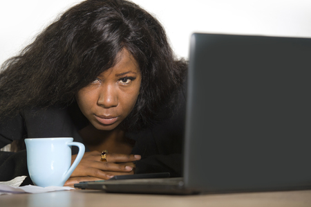 young depressed and overwhelmed black African American business woman working in stress at office computer desk feeling upset and overworked suffering depression and anxiety problem