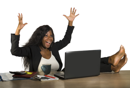 lifestyle office portrait of young happy and attractive black afro American businesswoman working excited with feet on computer desk smiling relaxed celebrating business financial success Stockfoto