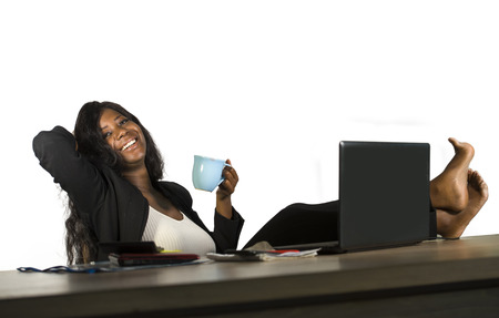 lifestyle office portrait of young happy and attractive black afro American businesswoman with feet on computer desk smiling relaxed in business success isolated on white background