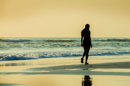 silhouette of young sporty woman walking on seashore after running workout at a beautiful beach enjoying sunset light and relax in fitness and healthy lifestyle concept