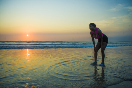 young sporty and tired African American runner woman cooling off breathing exhausted after running workout at beautiful beach sunset in healthy outdoors fitness activity Stock Photo