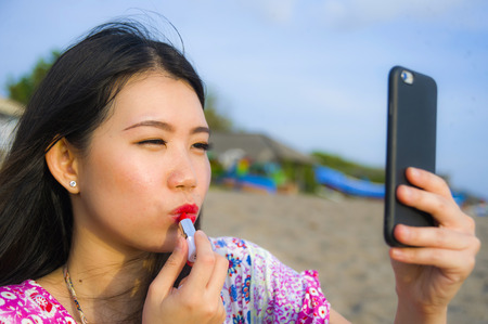 young happy and beautiful Asian Chinese woman retouching her makeup applying red lipstick on her lips using mobile phone as mirror at tropical paradise beach during summer holidays travel