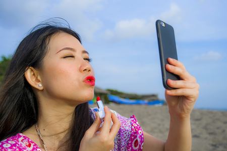 jeune femme chinoise asiatique heureuse et belle retouchant son maquillage en appliquant du rouge à lèvres rouge sur ses lèvres en utilisant un téléphone portable comme miroir sur la plage paradisiaque tropicale pendant les vacances d'été