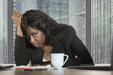young exhausted and depressed black African American business woman working upset and sad at office computer desk by the window in central financial district moody and frustrated