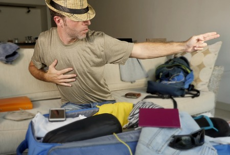 young happy and excited man packing suitcase and backpack preparing for holidays travel using summer hat for imitating dancing posture of famous pop star feeling crazy and playful Foto de archivo