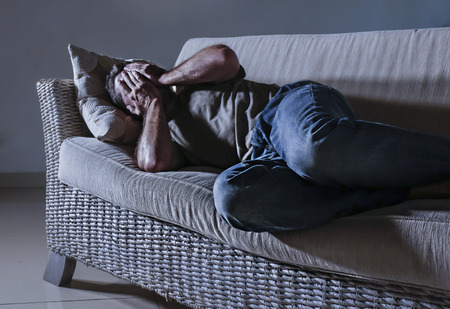 young desperate sad and frustrated man lying low at home sofa couch suffering depression problem and anxiety crisis crying helpless in pain feeling sick and unwell on dramatic light Stock Photo
