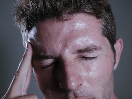 close up isolated portrait of young handsome and overwhelmed man suffering headache and migraine feeling sick and unwell touching his tempo in pain looking frustrated and stressed