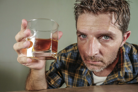 young attractive wasted and depressed addict and alcoholic man with whiskey glass thoughtful and sad failing resisting temptation to drink falling into alcohol abuse addiction and alcoholism problem