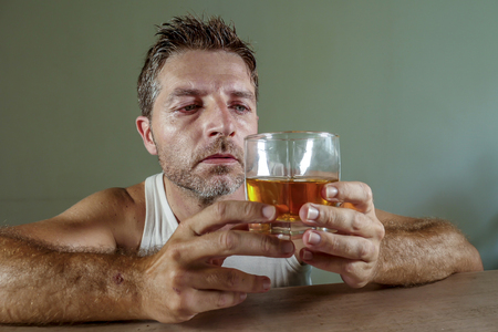 young wasted and depressed alcohol addict man in dirty singlet drinking glass of whiskey feeling desperate suffering alcoholism problem and booze addiction on isolated background in alcoholic concept