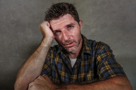 dramatic portrait of young sad and depressed man feeling anxious and overwhelmed crying desperate suffering depression problem and anxiety crisis isolated on grey background