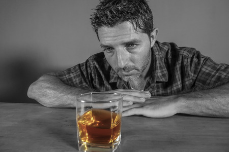 isolated black and white portrait of young messy depressed alcoholic man having a drink looking at whiskey glass feeling temptation of alcohol abuse in addiction and alcoholism problem Stock Photo