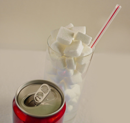 conceptual still life image of glass with straw full sugar cubes and soda refresh drink  in unhealthy nutrition sugar addiction and refreshments massive calories content isolated on studio background
