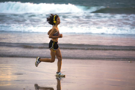 fit and athletic Asian Chinese sporty woman running on beautiful beach doing jogging workout on sunset in fitness healthy lifestyle and summer outdoors activity concept Stock fotó