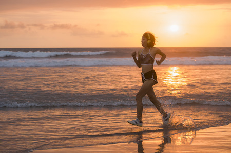 silhouette of fit and athletic Asian Chinese sporty woman running on beautiful beach doing jogging workout on sunset in fitness healthy lifestyle and summer outdoors activity concept Imagens