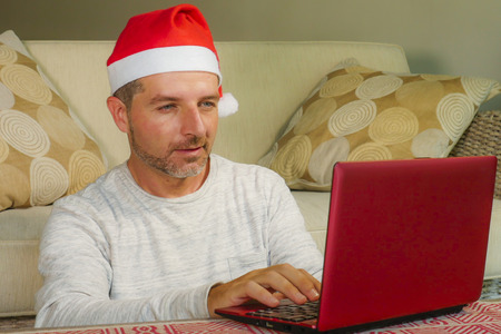 young handsome and attractive happy man in Santa hat at home online shopping on internet with laptop computer using credit card buying and paying Christmas present in ecommerce concept Фото со стока