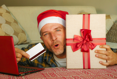 young handsome and attractive happy man in Santa hat at home couch using laptop computer and credit card holding Christmas gift box online shopping in ecommerce and internet business concept