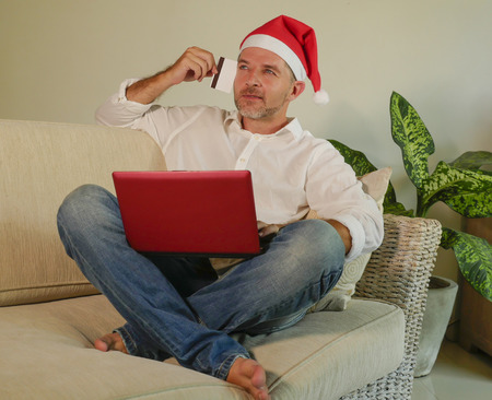 young attractive and happy man in Santa Klaus Christmas hat using laptop computer for buying xmas presents and gifts online with credit card in internet banking and electronic commerce and business