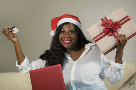 young happy and attractive black African American woman in Santa Klaus hat holding credit card and Christmas present box doing online shopping with laptop computer in internet business concept