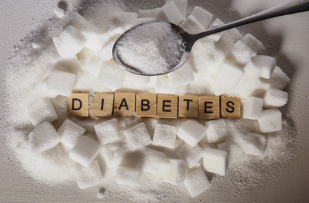 conceptual still life with pile of sugar cubes and diabetes word in block letters as advise on glucose excess and sweet unhealthy food abuse causing addiction and risk of disease and health problem