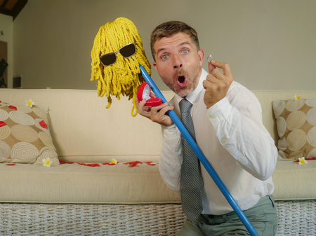 funny portrait of young weird crazy and happy man holding mop with sunglasses as if it was his fiance kneeling and proposing marriage offering engagement ring in wedding proposal parody Standard-Bild
