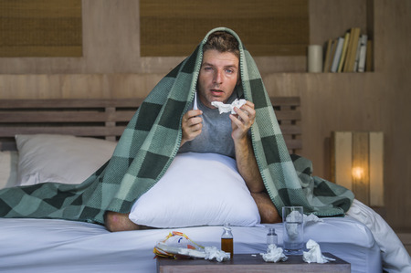 young sick wasted and exhausted man at home bed lying feeling unwell suffering cold and flu sneezing nose with tissues having virus and headache in domestic health care and grippe concept Stock Photo