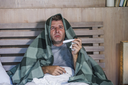 young sick wasted and exhausted man at home bed lying feeling unwell suffering cold and flu sneezing nose with tissues having virus and headache in domestic health care and grippe concept Stok Fotoğraf