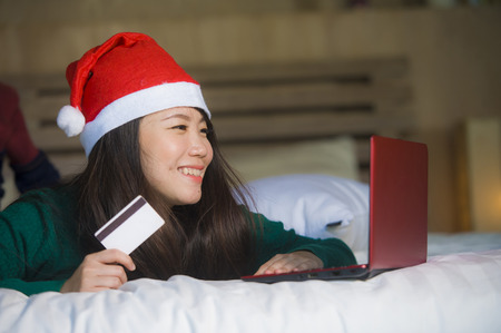 young happy and beautiful Asian Chinese woman in Santa Christmas hat using credit card and laptop computer for online shopping x-mas presents and gifts sitting joyful and excited on bed 스톡 콘텐츠