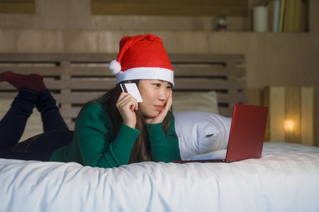 young happy and beautiful Asian Korean girl in Santa Christmas hat using credit card and laptop computer for online shopping x-mas presents and gifts sitting joyful and excited on bed