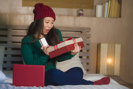 young beautiful and happy Asian Japanese girl holding credit card and Christmas gift box shopping online xmas presents smiling satisfied at home bed in e-business and e-commerce concept Stock Photo