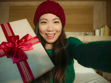 young beautiful and happy Asian Chinese woman taking selfie picture with mobile phone holding Christmas gift box smiling cheerful and excited in winter beamy at home celebrating xmas holidays