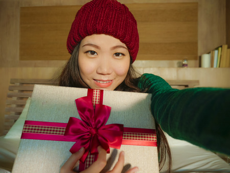 young beautiful and happy Asian Chinese girl taking selfie picture with mobile phone holding Christmas gift box smiling cheerful and excited in winter beamy at home celebrating xmas holidays Reklamní fotografie